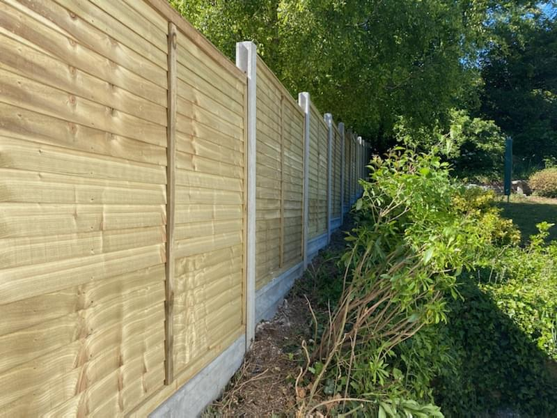 57 Straight edge panels with slotted concrete posts and gravel boards